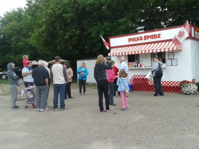 a long line up of people outside a red and white chip truck
