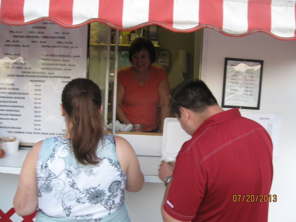 a smiling woman in a white and red booth with 2 people ordering food